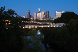 Downtown Houston skyline with Rosemont Bridge over Buffalo Bayou at night.