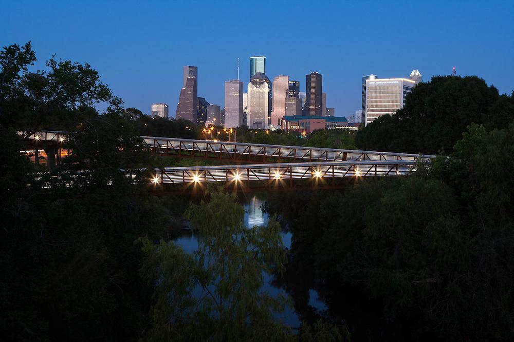 Downtown Houston skyline with Rosemont Bridge over Buffalo Bayou at night.