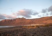 Evening sunset light on beach and cliffs La Caleta de Famara, Lanzarote, Canary islands, Spain