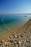 Mooring line and buouy with sea kayak and children playing in water, beach at Zlatni Rat, near Bol, island of Brac, Croatia