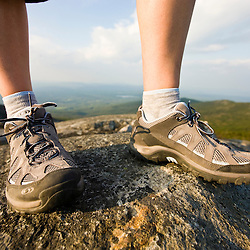 A hiker's feet on the summit of Mount Monadnock in Monadnock State Park in Jaffrey, New Hampshire.