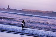 Surfer at the beach at dawn in Essaouira, Morocco.