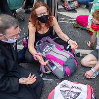 A group of participants in Christian Climate Action pray during a civil disobedience protest in Parliament Square in London. The three people in the photograph were all arrested by Police: Fr. Martin Newell, Ruth Jarman and Ben Buse.