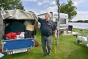 Nederland, Slijk-Ewijk, 3-6-2013Op camping De Grote Altena is men bezig de caravans die dicht aan het water staan te verplaatsten vanwege het verwachte hoogwater in de Waal. de heer Meijer uit Wierden bezig met inpakken van een aanhangertje. De caravan wordt door de camping verplaatst.Foto: Flip Franssen/Hollandse Hoogte