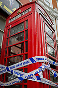 Police crime scene tape wrapped around a red phone box in Soho, on 8th March 2017, London borough of Westminster, England.