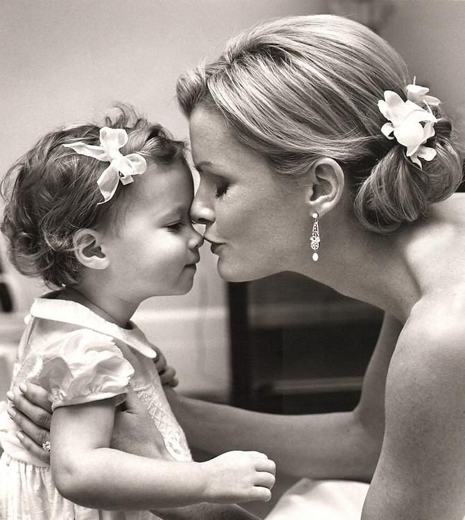Black and white photo of bride kissing cute little flower girl