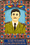 Tombstone of a Colonel,  The  Merry Cemetery ( Cimitirul Vesel ),  Săpânţa, Maramares, Northern Transylvania, Romania.  The naive folk art style of the tombstones created by woodcarver  Stan Ioan Pătraş (1909 - 1977) who created in his lifetime over 700 colourfully painted wooden tombstones with small relief portrait carvings of the deceased or with scenes depicting them at work or play or surprisingly showing the violent accident that killed them. Each tombstone has an inscription about the person, sometimes a light hearted  limerick in Romanian. .<br /> <br /> Visit our ROMANIA HISTORIC PLACXES PHOTO COLLECTIONS for more photos to download or buy as wall art prints https://funkystock.photoshelter.com/gallery-collection/Pictures-Images-of-Romania-Photos-of-Romanian-Historic-Landmark-Sites/C00001TITiQwAdS8