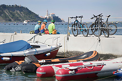 Bikers resting on jetty with bikes by inflatable raft