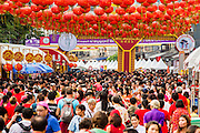 """10 FEBRUARY 2013 - BANGKOK, THAILAND:  The crowd on Yaowarat Road in Bangkok on Chinese New Year. The normally busy street, the main street in Chinatown is normally choked with traffic but it's closed to cars on Chinese New Year. Bangkok has a large Chinese emigrant population, most of whom settled in Thailand in the 18th and 19th centuries. Chinese, or Lunar, New Year is celebrated with fireworks and parades in Chinese communities throughout Thailand. The coming year will be the """"Year of the Snake"""" in the Chinese zodiac.   PHOTO BY JACK KURTZ"""