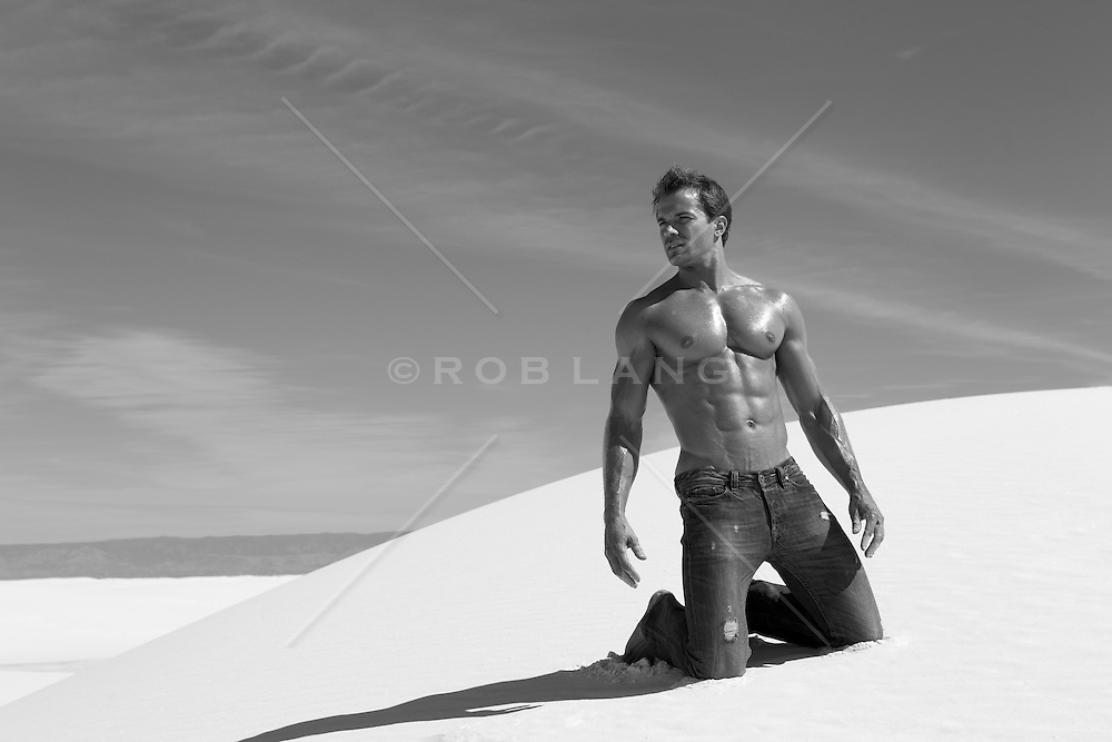 man without a shirt kneeling on a sand dune