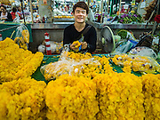 "11 AUGUST 2016 - BANGKOK, THAILAND:  A vendor makes marigold garlands for use in Buddhist rituals in the flower section of Pak Khlong Talat in Bangkok. Pak Khlong Talat (literally ""the market at the mouth of the canal"") is the best known flower market in Thailand. It is the largest flower market in Bangkok. Most of the shop owners in the market sell wholesale to florist shops in Bangkok or to vendors who sell flower garlands, lotus buds and other floral supplies at the entrances to temples throughout Bangkok. There is also a fruit and produce market which specializes in fresh vegetables and fruit on the site. It is one of Bangkok's busiest markets and has become a popular tourist attraction.        PHOTO BY JACK KURTZ"