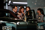 A Rolls-Royce Motor Cars Ltd. representative shows the features of a Phantom automobile to a group of female visitors during the China ( Guangzhou) International Automobile Exhibition in Guangzhou, Guangdong Province, China, on Monday, Nov. 21, 2011. Despite signs of slowing, China remains the largest and fastest growing market for international car makers, especially in the luxury sector.