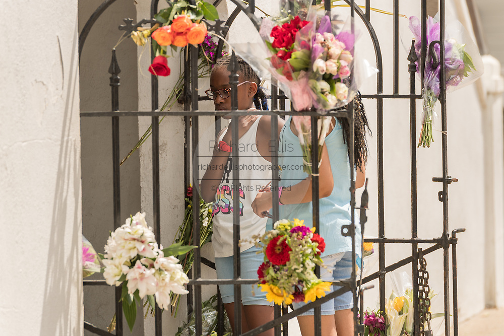 Young children view floral tributes left at the Mother Emanuel African Methodist Episcopal Church on the 2nd anniversary of the mass shooting June 17, 2017 in Charleston, South Carolina. Nine members of the historic African-American church were gunned down by a white supremacist during bible study on June 17, 2015.