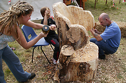 Newstead Tree Fest; group of people carving an armchair from a tree trunk,