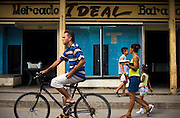 """People go past a store with empty displays called """"Market Ideal"""" in Baracoa, Cuba on Saturday July 12, 2008."""