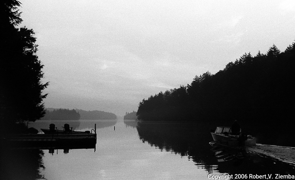 """""""The Flow""""-A black and white image of a small boat heading out on the lake passing a dock."""