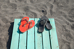 two pair of flip flops on a wooden walkway at beach in Greece