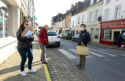 02 April 2020. Hesdin, Pas de Calais, France. <br /> Coronavirus - COVID-19 in Northern France.<br /> <br /> Locals say hello in the almost deserted streets of Hesdin, a usually bustling and vibrant town, especially on Thursday's when a large outdoor market fills the 'Place D'Armes' and side streets.  Despite an easing of restrictions on local markets the streets were mostly empty. <br /> <br /> For the first time since government restrictions came into force, the main market in Hesdin has been permitted to re-open. The historical town has hosted a usually vibrant and bustling market since the middle ages. With stall holders limited and many suffering huge financial losses, those selling food today were happy to be back to work despite the ongoing risks posed by coronavirus.<br /> <br /> Shoppers, many wearing masks were mostly maintaining their social distancing with people happy to be out and able to meet and talk with other people. A lot of shoppers were elderly people who have been trapped in their homes for weeks. One shopper complained of 'la misère,' - the misery of this virus and being stuck in her home. <br /> <br /> Anyone leaving their home must carry with them an 'attestation,' in a effect a self administered permit to allow them out of the house. If stopped by the police, one must produce a valid permit along with identification papers. Failure to do so is punishable with heavy fines. Movement in France has been heavily restricted by the government and today's market re-opening was a brief return to normalcy for many able to escape the confines of their homes.<br /> <br /> Photo©; Charlie Varley/varleypix.com