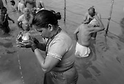 A Hindu devotee prays at the Sangam, the confluence of the rivers Ganges, Yamuna, and mystical Saraswati at Kumbh Mela in Prayagraj, India.