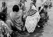 Hindu devotees take a holy bath in the Sangam, the confluence of the Ganges, Yamuna, and mythical Saraswati rivers during Kumbh Mela in Prayagraj, India.