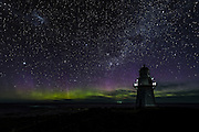 Vertical rays radiate from the Aurora Australis at Waipapa Point Lighthouse in the Catlins, New Zealand.