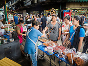 02 SEPTEMBER 2015 - BANGKOK, THAILAND: People buy precooked food at a street food stall in Bang Chak market. The Bang Chak Market serves the community around Sois 91-97 on Sukhumvit Road in the Bangkok suburbs. About half of the market has been torn down, vendors in the remaining part of the market said they expect to be evicted by the end of the year. The old market, and many of the small working class shophouses and apartments near the market are being being torn down. People who live in the area said condominiums are being built on the land.         PHOTO BY JACK KURTZ
