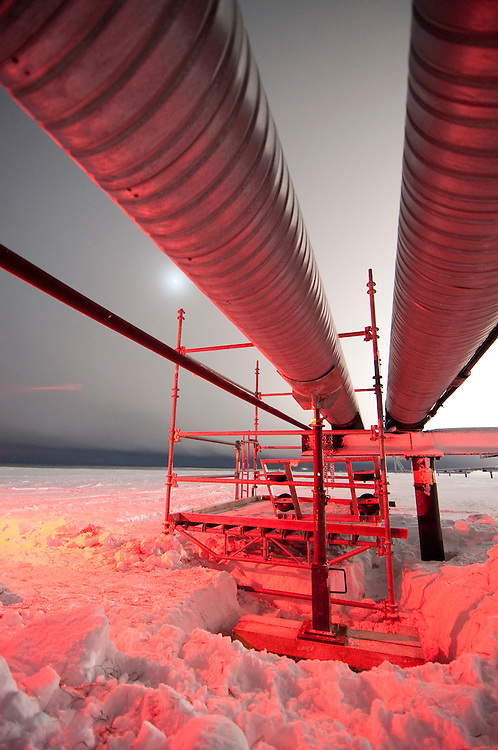 Alaska, North Slope. A line lift for pipeline corrosion inspection gets set in place with red brake lights coloring pipe.