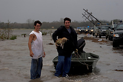 24 Sept 2005. Louisiana/Texas border. Hurricane Rita aftermath. <br /> <br /> Route 27, Louisiana where the storm hit hardest on the Louisiana/Texas border. The back edge of Rita floods across the roadway as rescue workers attempt to reach stranded flood victims. L/R Josh Herman and his uncle Romeo Espinosa try to get to their flooded convenience store in Carlyss with an abandoned puppy they rescued and named Rita.<br /> Photo; ©Charlie Varley/varleypix.com