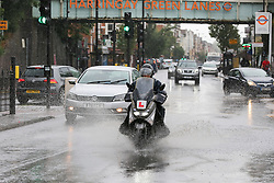 © Licensed to London News Pictures. 18/06/2020. London, UK. A motorbike rides through a flood on Green Lanes, north London during heavy downpour. Photo credit: Dinendra Haria/LNP