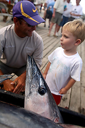 07 May 2010. Venice, Louisiana. Deepwater Horizon, British Petroleum environmental oil spill disaster.<br /> Bobby Warren and Evan Ballay (3 yrs) admire yellow fin tuna and other predator species caught by sport fishermen to the west of the giant BP oil spill. Nobody is sure how much longer they will be able to catch fish in the region. Charter boat captains, rental camps and hotels are reporting mass cancellations of fishing trips and other vacations to the Gulf  Coast region.<br /> Photo credit;Charlie Varley/varleypix.com