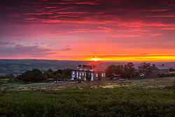 © Licensed to London News Pictures. 07/09/2020. Ilkley UK. The sun briefly breaks through the clouds as the sky glows red at sunrise this morning above the Cow & Calf pub on Ilkley Moor in Yorkshire. Photo credit: Andrew McCaren/LNP