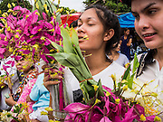 """22 JULY 2013 - PHRA PHUTTHABAT, THAILAND: A woman holds flowers before presenting them to monks during the Tak Bat Dok Mai at Wat Phra Phutthabat in Saraburi province of Thailand, Monday, July 22. Wat Phra Phutthabat is famous for the way it marks the beginning of Vassa, the three-month annual retreat observed by Theravada monks and nuns. The temple is highly revered in Thailand because it houses a footstep of the Buddha. On the first day of Vassa (or Buddhist Lent) people come to the temple to """"make merit"""" and present the monks there with dancing lady ginger flowers, which only bloom in the weeks leading up Vassa. They also present monks with candles and wash their feet. During Vassa, monks and nuns remain inside monasteries and temple grounds, devoting their time to intensive meditation and study. Laypeople support the monastic sangha by bringing food, candles and other offerings to temples. Laypeople also often observe Vassa by giving up something, such as smoking or eating meat. For this reason, westerners sometimes call Vassa the """"Buddhist Lent.""""     PHOTO BY JACK KURTZ"""