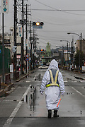 A security guard controls traffic on a road in Namie Town inside the Fukushima exclusion zone, Namie, Fukushima, Japan. Wednesday March 9th 2016. The Great East Japan Earthquake on March 11th 2011 was followed by a massive tsunami that levelled much of the Tohoku coast in north east Japan, killing around 18,000 people and causing meltdowns and explosions at the Fukushima Daiichi nuclear power station leading to the contamination and evacuation of a 20 kilometre exclusion zone around the plant.