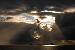 © Licensed to London News Pictures. 23/11/2019. Plymouth, UK. A ship is seen illuminated by rays of sunshine bursting through broken cloud following a rainstorm on Plymouth Sound , off the coast of Devon . Photo credit: Joel Goodman/LNP