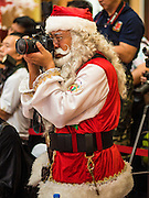 17 SEPTEMBER 2015 - BANGKOK, THAILAND:  HUNG SHING JOHNNY, a Santa Claus from Hong Kong, takes a picture at the World Santa Claus Congress in Bangkok. Twenty-six Santa Clauses from around the world are in Bangkok for the first World Santa Claus Congress. The World Santa Claus Congress has been an annual event in Denmark since 1957. This year's event, hosted by Snow Town, a theme park with a winter and snow theme, hosted the event. There were Santas from Japan, Hong Kong, the US, Canada, Germany, France and Denmark. They presented gifts to Thai children and judged a Santa pageant. Thailand, a Buddhist country, does not celebrate the religious aspects of Christmas, but Thais do celebrate the commercial aspects of the holiday.   PHOTO BY JACK KURTZ