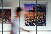 A man walks past photograph of a scene from the cultural revolution in Dazhanzi. China's art scene is becoming popular among foreign art collectors pushing prices higher.