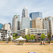A man lays in the dead grass at Romare Bearden Park in Uptown Charlotte hours before the first pitch is thrown out at the new Knights stadium.