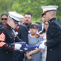 U.S. Marine Corps members fold a flag to present to state Sen. John Pinto's family following the funeral Mass at Sacred Heart Cathedral, Thursday, May 30 in Gallup.