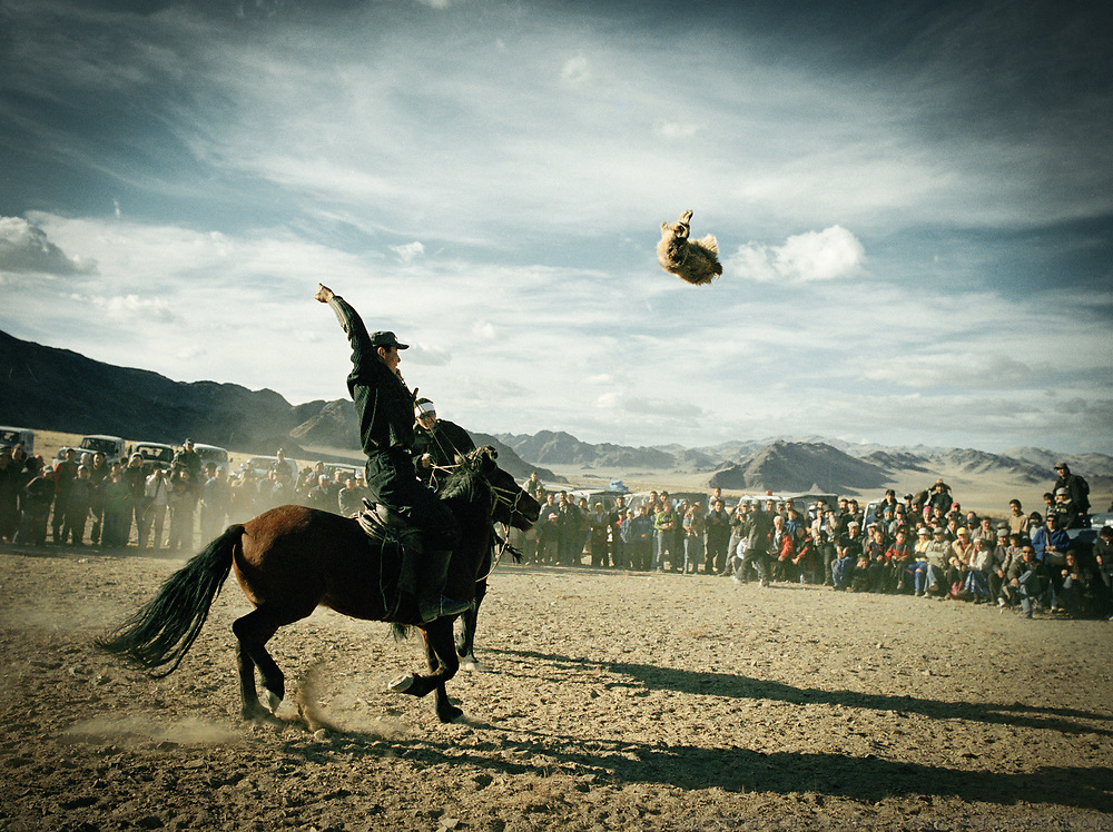 A horse rider throws a sheep skin in the air after catching it in a game of Buzkachi.<br /> <br /> Eagle Hunting festival in Western Mongolia, in the province of Bayan Olgii. Mongolian and Kazak eagle hunters come to compete for 2 days at this yearly gathering. Mongolia