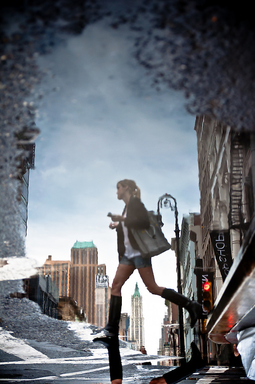 Reflection in a puddle of a woman crossing Broadway Avenue in Manhattan