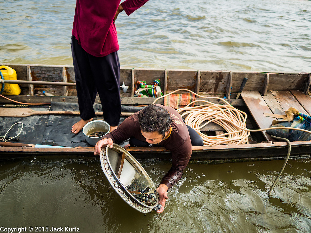 14 OCTOBER 2015 - BANGKOK, THAILAND: A spotter stands in the boat while the diver he works with sluices things he brought up from the bottom of the Chao Phraya River in Bangkok, looking for anything he can sell. Divers work in two man teams on small boats in the Chao Phraya River. One person stays in the boat while the diver scours the river bottom for anything that can be salvaged and resold. The divers usually work close to shore because the center of the river is a busy commercial waterway with passenger boats and commercial freight barges passing up and down the river all day long. The Chao Phraya is a dangerous river to dive in. It's deep, has large tidal fluctuations, is fast flowing and badly polluted. The divers make money only when they sell something.    PHOTO BY JACK KURTZ