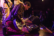 """Sammo tunes his steel guitar,setting up to play with lex Battles and The Whisk Rebellion. The label on his guitar reads """"This Tin Can Eats emo Bands."""""""