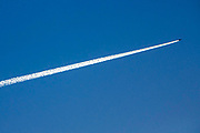 An aeroplane flying high across a blue sky producing a striking contrail cloud behind it on the 19th of January 2016, Folkestone, United Kingdom.  Contrails are clouds formed when water vapour condenses and freezes around small particles aerosols that exist in aircraft exhaust. Some of that water vapour comes from the air around the plane; and some is added by the exhaust of the aircraft. The exhaust of an aircraft contains both gas vapour and solid particles.