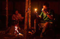 Kichwa villagers drinking traditional Guayusa tea before sunrise in Anangu, Yasuni National Park, Orellana Province, Ecuador. Kichwa drink this tea every morning and share their dreams with each other in order to help plan their day.