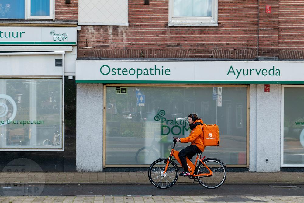 In Utrecht rijdt een meisje op een elektrische fiets voor Thuisbezorgd.nl.<br /> <br /> In Utrecht a girl delivers food with an e-bike.