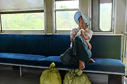 A woman sleeping inside a carriage on the Yangon Circular Railway on 16th May 2016 in Yangon, Myanmar. The railway, a narrow gauge local commuter trail network serving Yangon metropolitan area is a 28.5 mile 45.9 km 39 station loop system. This British built rail-loop connects Yangon to its satellite towns and villages