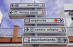 Direction signs in Spanish indicating location of market; police station and town centre,
