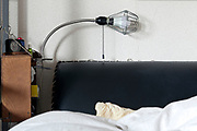 corner of bed with lamp and alarm clock