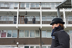 © Licensed to London News Pictures 08/04/2021. Mottingham, UK. Two police officers stand guard outside a flat.  A Met Police investigation is underway after a twenty year old woman was found dead yesterday in a flat on a south East London housing estate in Mottingham. A large number of police officers wearing forensic suits are searching the estate for evidence. A number of police cordons are in place. Photo credit:Grant Falvey/LNP