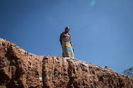 A woman waits to receive some material to separete cobalt from sand in a mine between Lubumbashi and Kolwezi, May 31, 2015. AFP PHOTO/FEDERICO SCOPPA